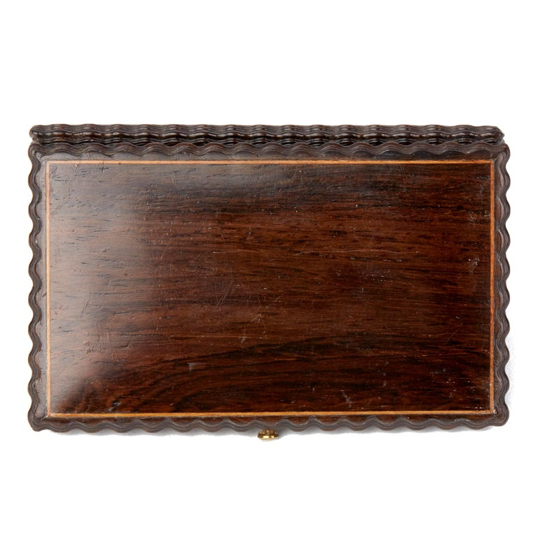 A very fine antique carved rose wood needle case with hinged cover with spring clasp and with central inset brass cartouche, the edges of the box with finely carved detail and with inset contrasting wood piping around the edges of the top and base