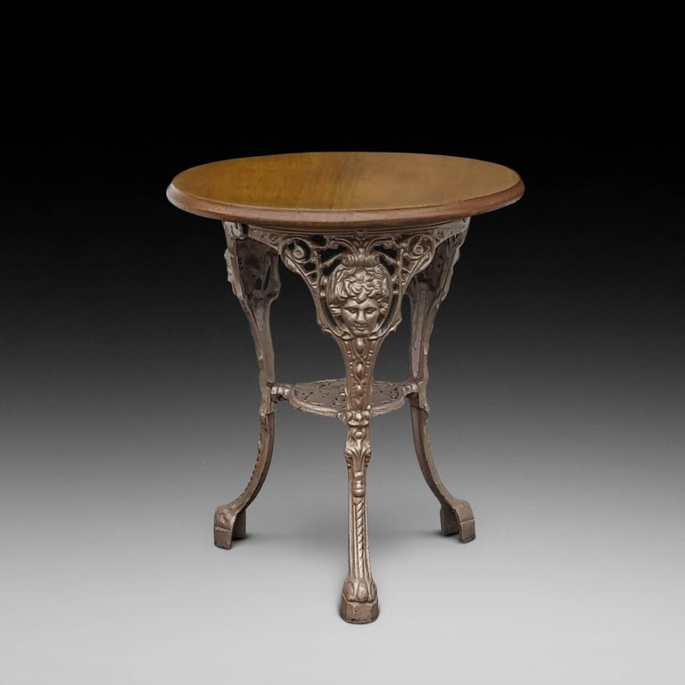 Victorian cast iron garden table with mahogany top decorated with Britannia Cast portrait, hearts and lion paw feat