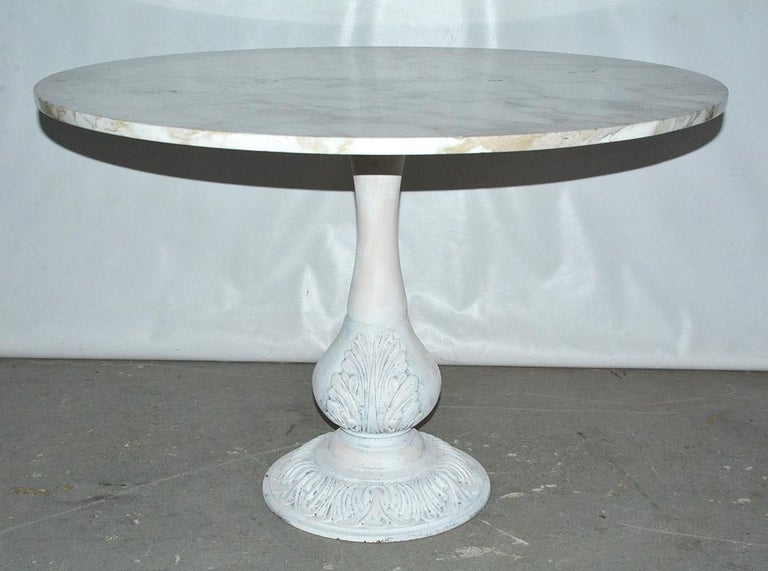 The Victorian cast iron table base painted white has a secured square masonite board, on which sits a veined white marble round top. The base is adorned with acanthus leaves. Picture the table for either indoor or outdoor placement. Table is