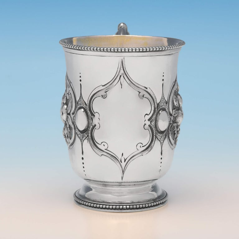 Hallmarked in London in 1866 by Henry Holland, this very attractive, Victorian, antique sterling silver christening mug, features chased and engraved decoration to the sides, a gilt interior and bead borders. The christening mug measures