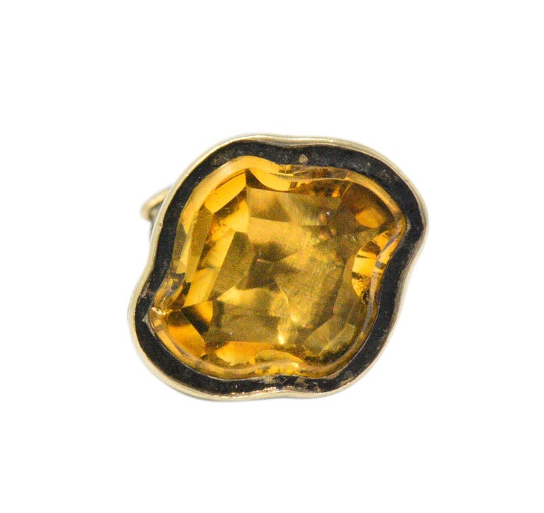 With a polished, modified quatrefoil shaped citrine  With scrolling and engraved gold details  Tested as 14 karat gold  Measures: Approx. 3/4 x 1/2 Inches  Total Weight: 2.4 Grams  Petite. Appealing. Handsome.         Stock Number: We- 1742