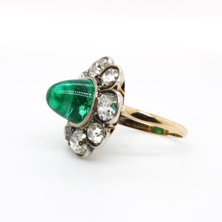 Victorian Colombian Cabochon Emerald and Diamond Ring, ca. 1880s  The beautiful Victorian high cabochon emerald (ca. 6.5 carats, Colombian) is a very clean and bright stone with a beautiful crystal. It is surrounded with petals of old European cut