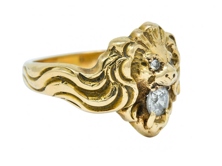 Band ring is highly rendered to depict a roaring lion with a whiplashed mane  Diamond accented eyes and an old European cut diamond clenched in its jaws  Weighing in total approximately 0.28 carat with J color and SI clarity  With maker's
