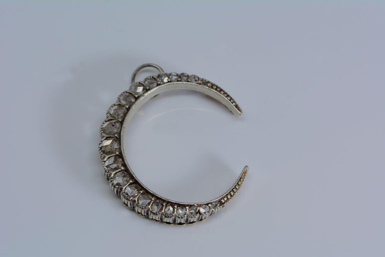 This beautiful crescent represents the moon goddess, (Artemis, Diana triformis, Luna) glowing and divine.  Most crescent pendants or brooches we have seen are usually silver backed with yellow gold, or just yellow gold, but this one is platinum