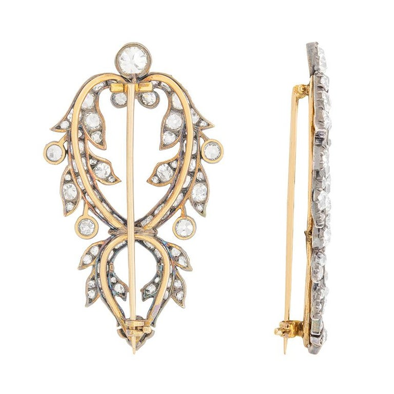 These beautiful brooches make a double clip set and date back to the 1800s. They would have most likely been worn on the lapels of a upper class gentleman or woman for a special occasion. There is a 0.60 carat diamond at the top of each brooch,