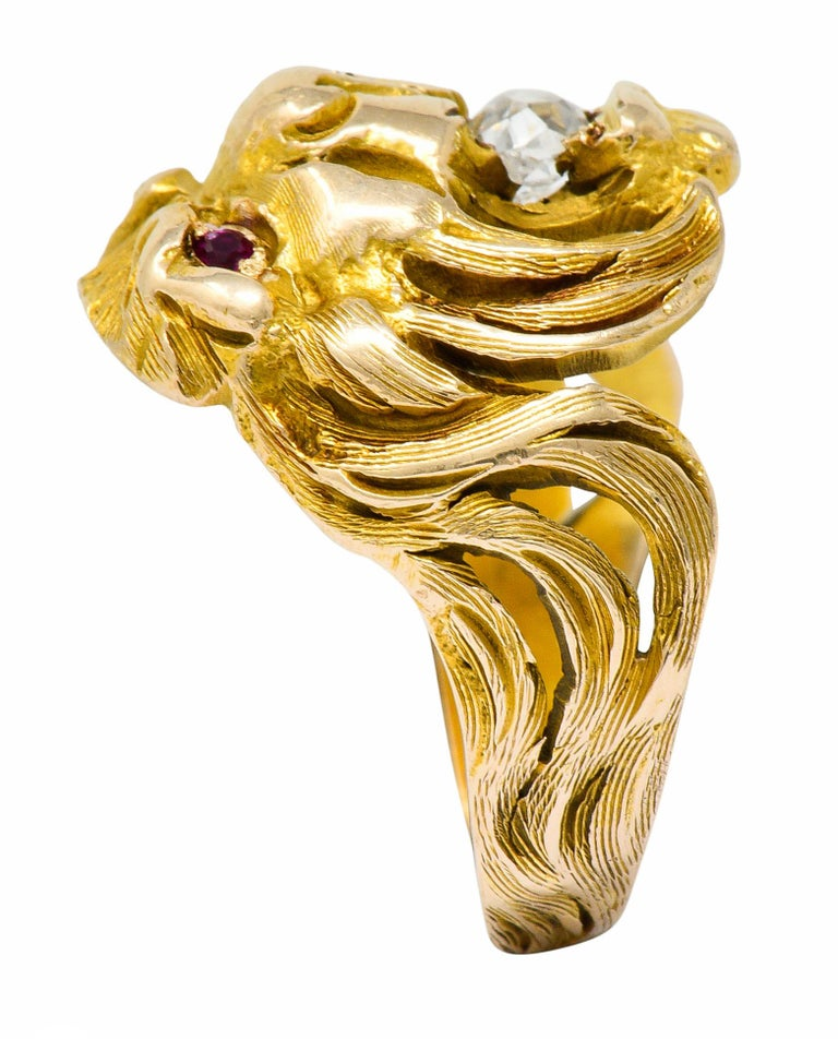 Band ring is highly rendered to depict a roaring lion with a flowing mane  With an old mine cut diamond clutched in its jaws weighing approximately 0.33 carat; I color with SI clarity  Accented by round cut ruby eyes; well-matched and bright