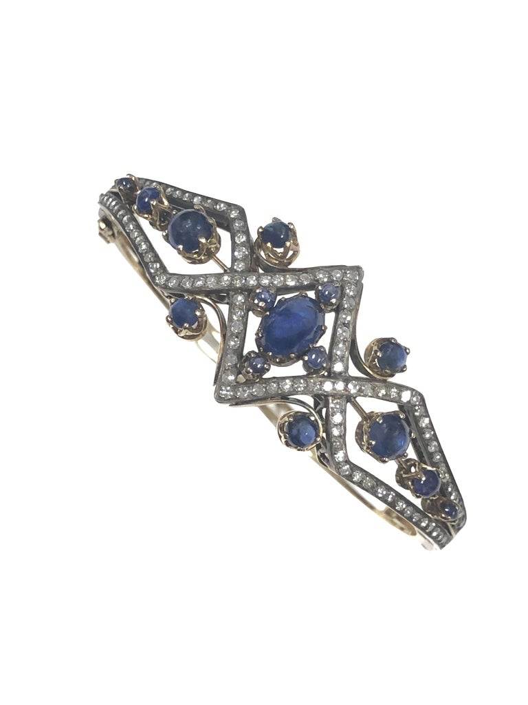 Circa 1910 Bangle Bracelet, 15K Yellow Gold with a Silver top, set with Old cut Diamonds totaling approximately 1.25 Carats and further set with very Fine color Cabochon Sapphires. Measuring just under 1 inch wide at the very center of the top and