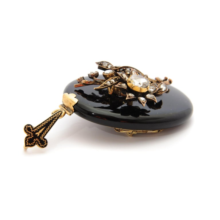 Amazing onyx locket pendant with many diamonds. This locketpendant has on top a bouquet applique with many rose cut diamonds,approximately 0,60 carats in total. This 14 karat gold pendant can also be worn as a brooch.At the back a glass plate
