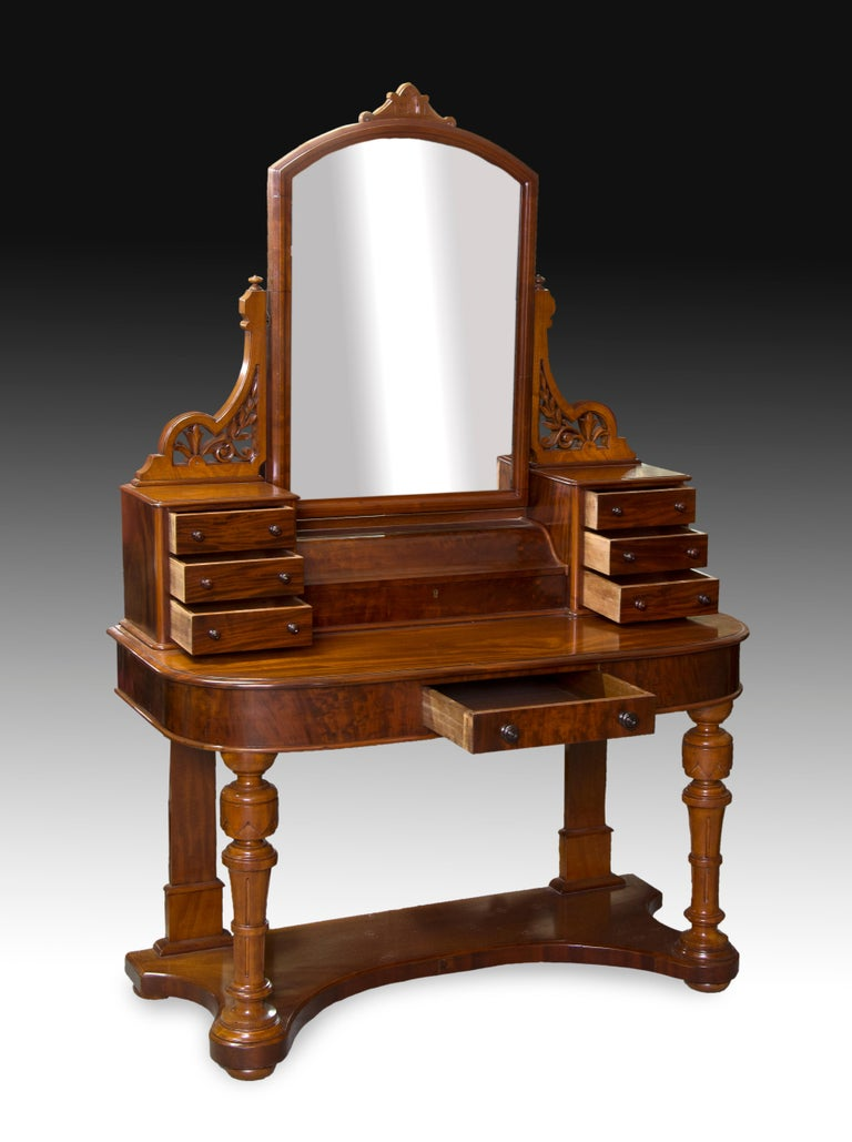 Vanity unit made of mahogany carved wood with the front legs turned as clusters topped by vase-shaped pieces, drawer on the front and a recessed upper body with three drawers on each side and a space closed to the center, under the rectangular