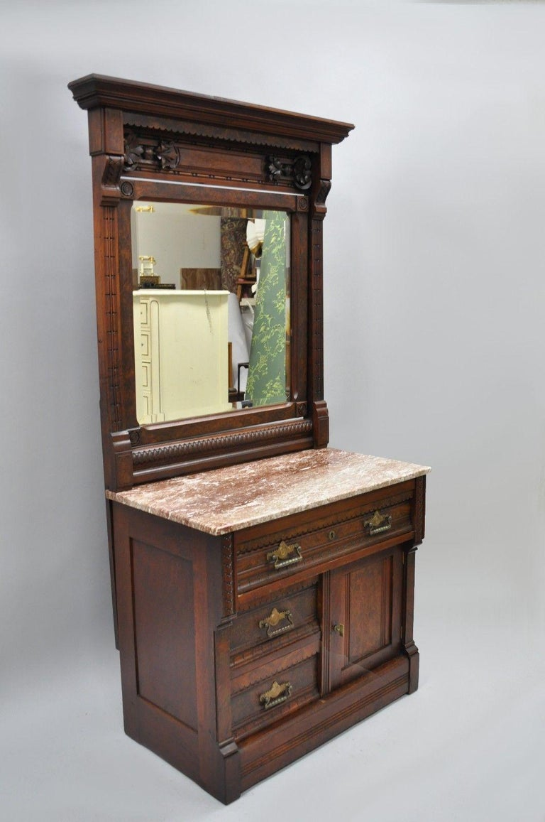 Antique Eastlake Victorian burl walnut marble-top wash stand chest with mirror. Item features beautiful wood grain, pivoting beveled glass mirror, marble top, three dovetailed drawers, and one swing door, circa mid-1800s. Measurements: 68