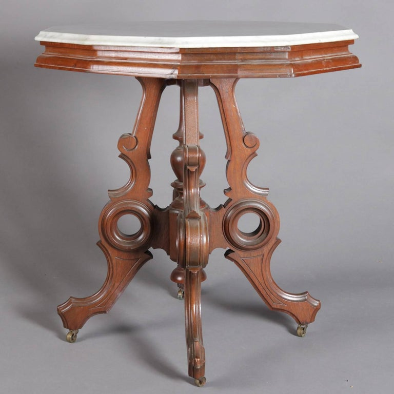 Victorian Eastlake parlor table features beveled marble top above incised and carved and pierced walnut base with incised decorated stylized scroll form legs with turned center plinth, 19th century  ***DELIVERY NOTICE – Due to COVID-19 we are