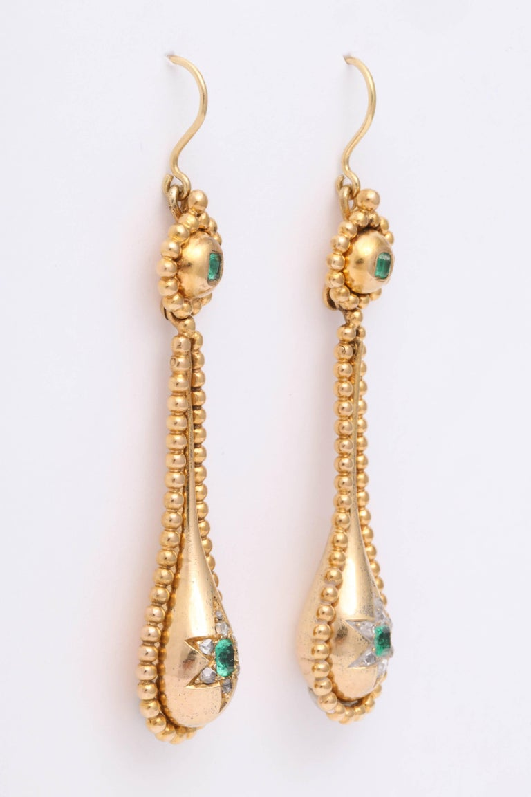 English earrings set with emeralds and diamonds in 18K yellow gold dating to the Victorian era.