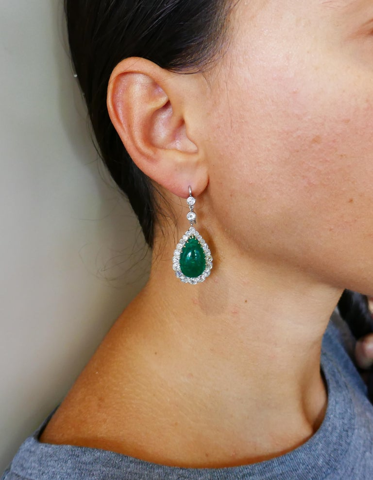 Classic emerald and diamond dangle earrings that are a great addition to your jewelry collection. The earrings are made of 14 karat (tested) yellow gold and silver and feature cabochon emeralds framed with a row of old-mine and Old European cut
