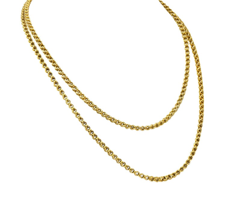 Rolo style chain necklace comprised of doubled round links that are deeply grooved  Completed by a barrel clasp featuring decorative black enamel detail  Tested as 10 karat gold  Length: 34 inches  Width at widest: 3/16 inch  Total weight: 21.0