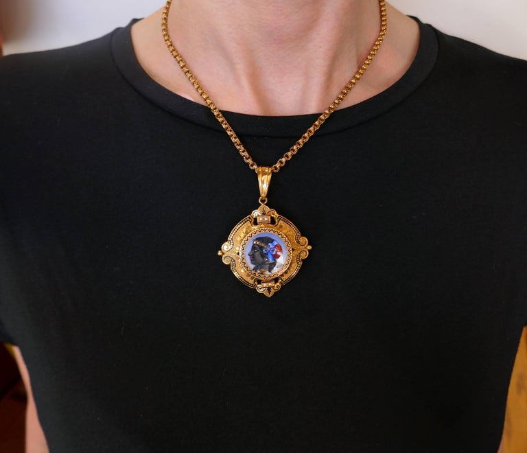 Amazing Victorian pin/necklace created in the 1900's. Features a handmade enamel painting depicting a woman's profile wearing a diamond diadem and earrings, and colorful head scarf. The painting is framed in yellow gold, accented with black enamel