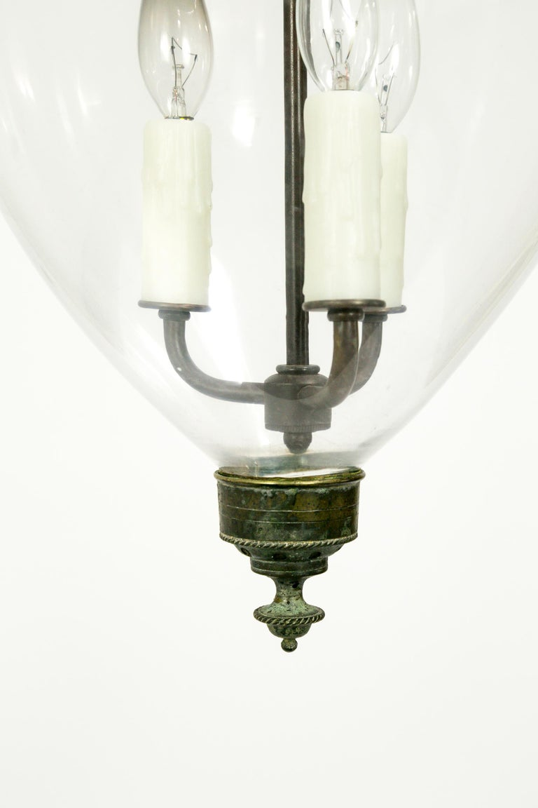 An elegant English bell jar lantern with refined details on the brass hardware: a ribbed glass holder with bird head chain hooks, and a rope-trimmed finial. The brass has a beautiful, aged patina. Handblown jar and smoke bell. 3-light candelabra