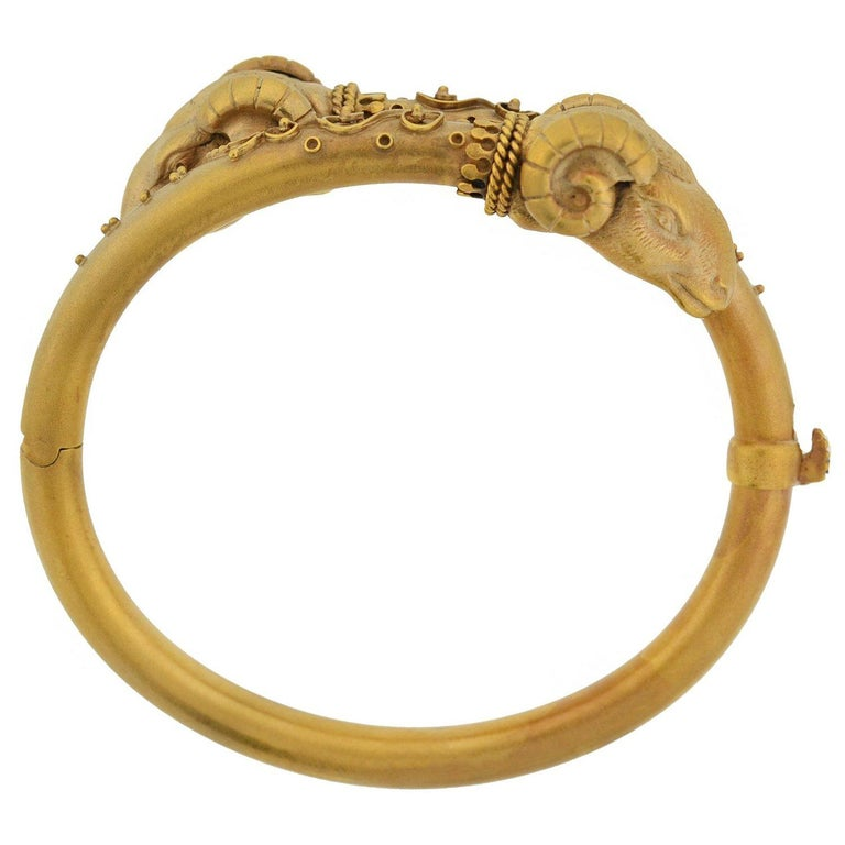 An impressive statement bracelet from the Victorian (ca1880) era! Crafted in 14kt gold, the bangle incorporates a double ram's head motif into a stylish bypass design. Each 3-dimensional ram's head is incredibly detailed, including curling horns,