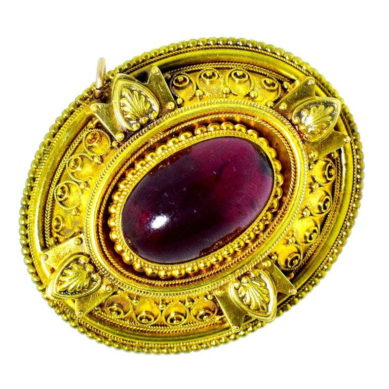 Etruscan, from the last quarter of the Nineteenth Century, large gold antique brooch centering a carbuncle natural garnet weighing approximately 9 cts., and surrounded by fine bead and wire work, Etruscan Revival.  On the verso, is the original hair