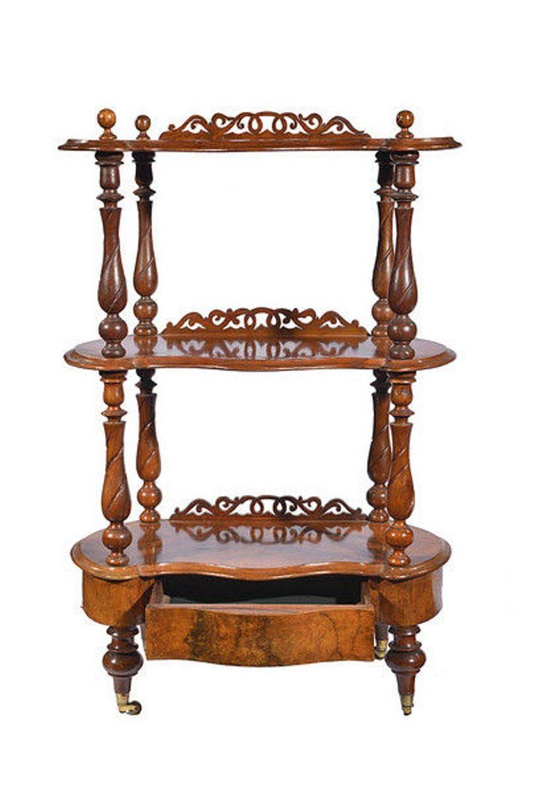 A late Victorian kidney shaped three tier figured walnut whatnot with a concealed fitted drawer to the base. Each tier with an open fretwork upstand to the back. The whole raised on turned supports ending on brass casters.