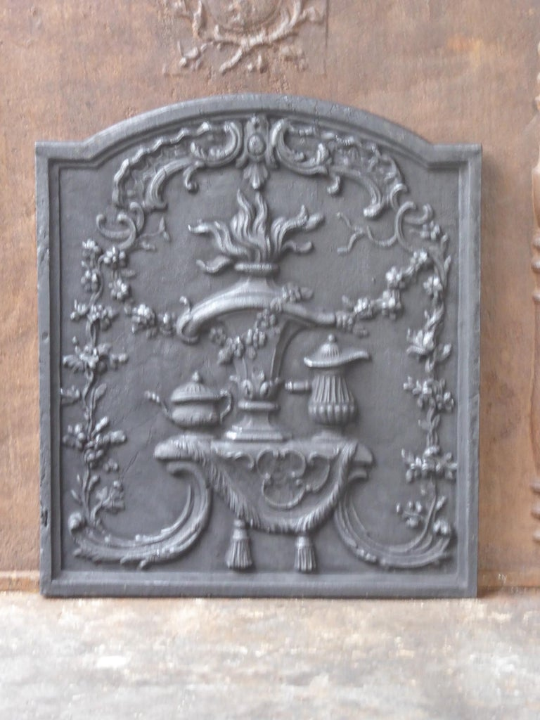 Early 20th century Victorian fireback with a fire pot surrounded by various decorations. The fireback is made of cast iron and has a black patina. The fireback is in a good condition and does not have cracks.