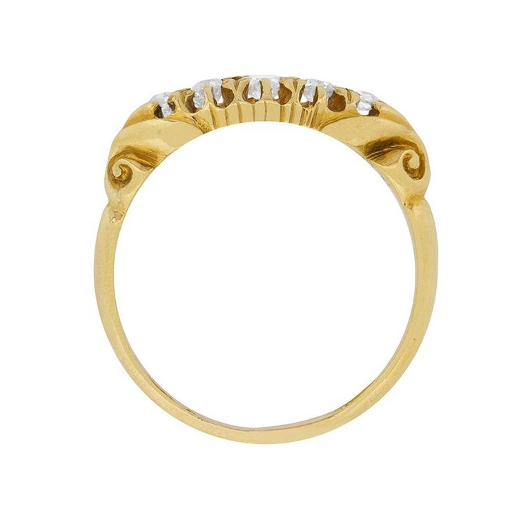 A classically Victorian five stone ring with a lovely carved shank detailing. The diamonds are graduating in size from the centre and have a total carat weight of 0.24 carat. The diamonds are old cut, which adds to the history of these piece and are