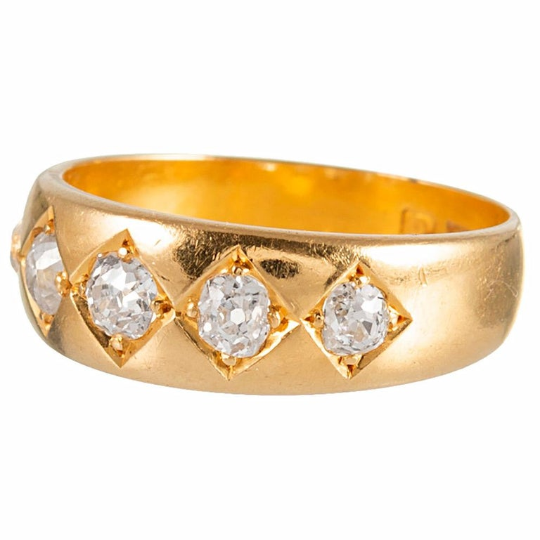 This Victorian band of 18 karat yellow gold is adorned with five old mine cut diamonds weighing .75 carats in total. The round stones are nestled in squares, creating a quilted look and augmenting the visual presence of the diamonds. The numerous