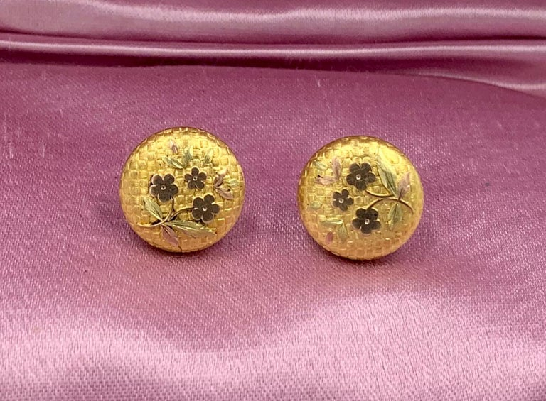 A rare pair of Etruscan Revival Victorian Flower Motif Earrings in 10 Karat Gold.  The exquisite earrings have an engraved checkerboard background with a flower and leaf motif.   The gold work is stunning and the warm color of the antique Victorian