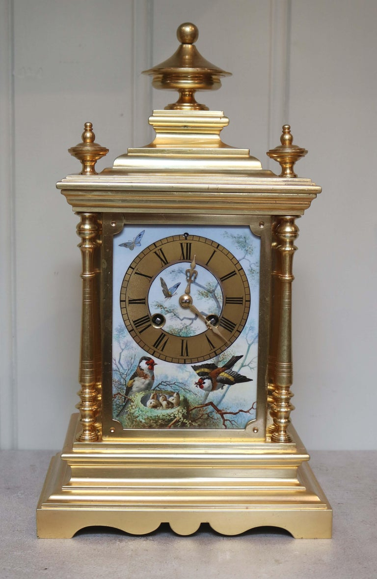 A lovely decorative mantel clock typical of high Victorian sentiment. It has a classic gilt brass step moulded case with side columns and beautifully hand decorated porcelain panels depicting nesting and birds in song and butterflies. It has an 8