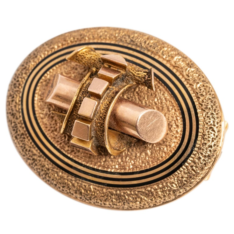 The rose gold brooch of textured surface enhanced with concentric black enamel bands, the reverse fitted with a gold hook and pin attachment. Perfect on a scarf or lapel, as a clasp shortener or suspending a pendant watch.  American or English   1 ¼