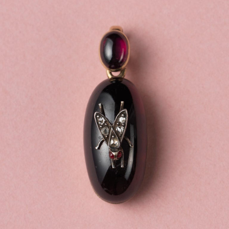 A 14-carat gold locket with a larger oval, cabochon-cut garnet decorated with a silver and diamond fly; the hoop is also set with a smaller cabochon-cut garnet, at the back is an oval locket with one glassed compartment. England, end 19th