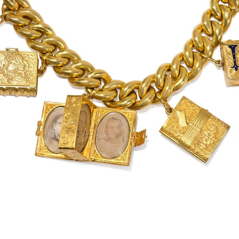 An antique gold curb link bracelet suspending seven book form locket pendants, each locket featuring elaborately embossed surfaces and containing multiple picture compartments - some still with vintage photos - in 18k.