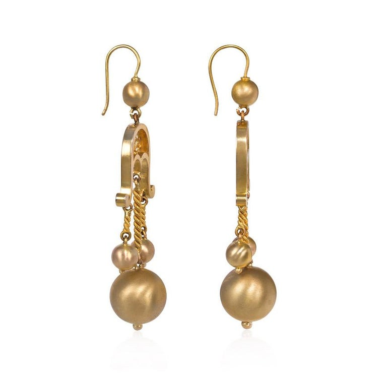 A pair of antique gold earrings of girandole design comprised of three ball pendants suspended from a scrolled openwork surmount, in 14k.