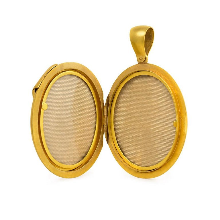 An antique oval gold locket pendant with diamond-accented belt buckle motif and two interior compartments, in 15k.  England.  (Chain not included.)  Dimensions: 2 3/8