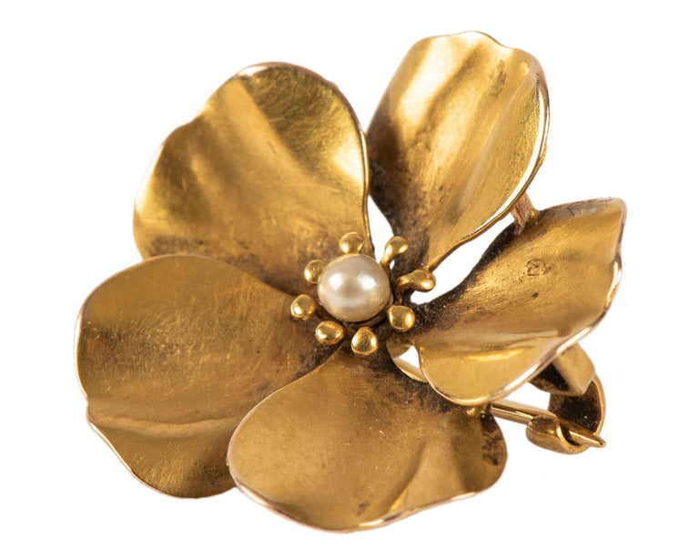 A small gold pansy pin with overlapping petals of matte gold centering a seed pearl.  American, circa 1890  5/8 in. (1.6 cm) diam.