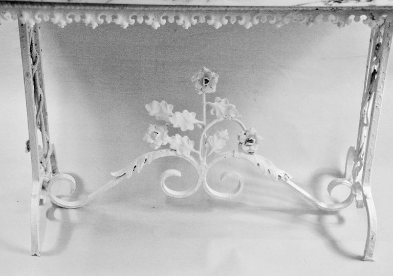 3-622 Victorian iron based table with floral detailing. Marble top is newer Can be used as a coffee table indoors or as a garden table.