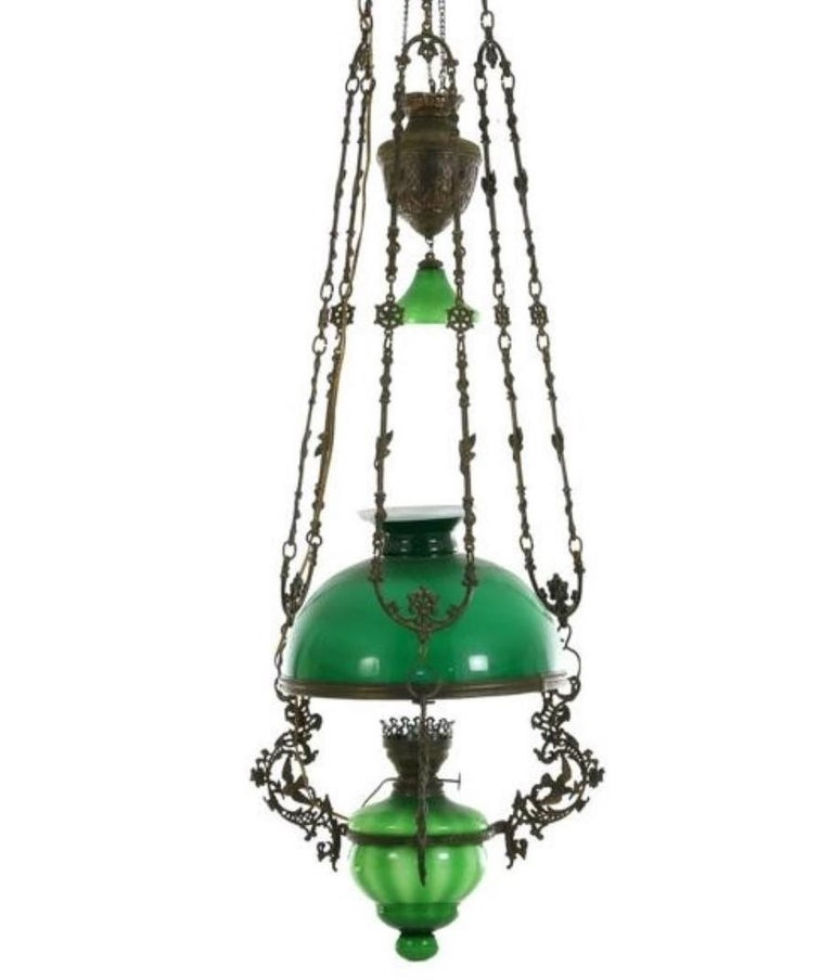A fine Victorian bronze and green glass hanging oil lamp converted to electric, England, mid-19th century. With a large green hurricane shade and clear glass hurricane chimney. This beautiful lamp comes from a country house library in South West