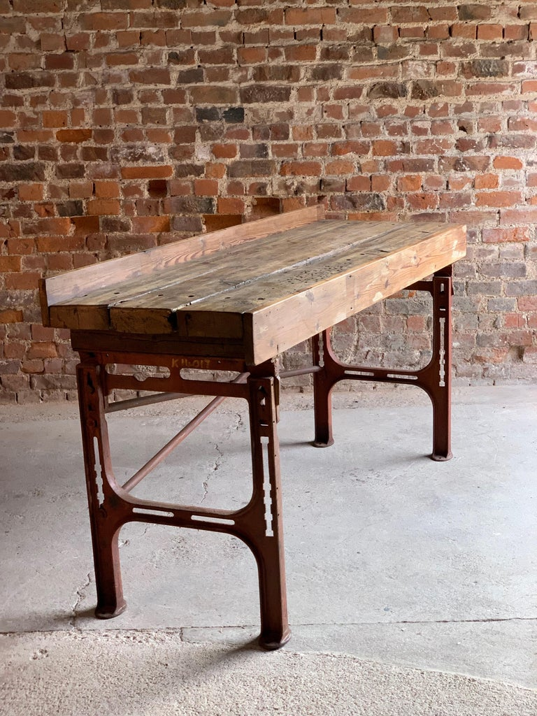 Victorian Industrial workbench table dating to circa 1868  Industrial oak and cast iron workbench table circa 1868, the distressed three plank top over brick coloured cast iron stand with X-frame stretchers, ideal as a console table, media stand