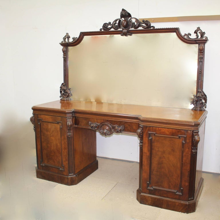 A stunning Victorian mahogany mirrored sideboard. Having a large carved mirror with central cartouche crest and flanked by decorative columns with floral and corbel decoration. The top with canted corners stands above a nicely carved central drawer.