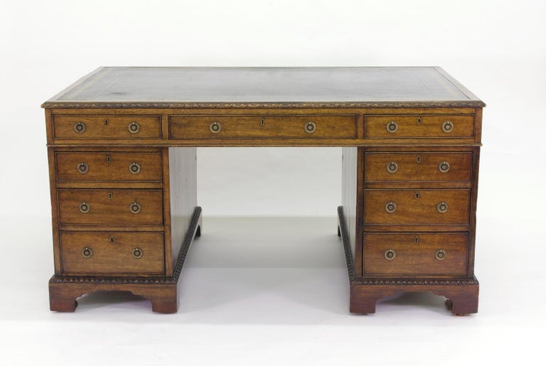 Victorian mahogany partners desk, the green tooled leather top with carved edge over three drawers; the pedestals with three graduated doors to one side and doors to the other, opening to a single shelf, all on bracket feet with egg and dart carving