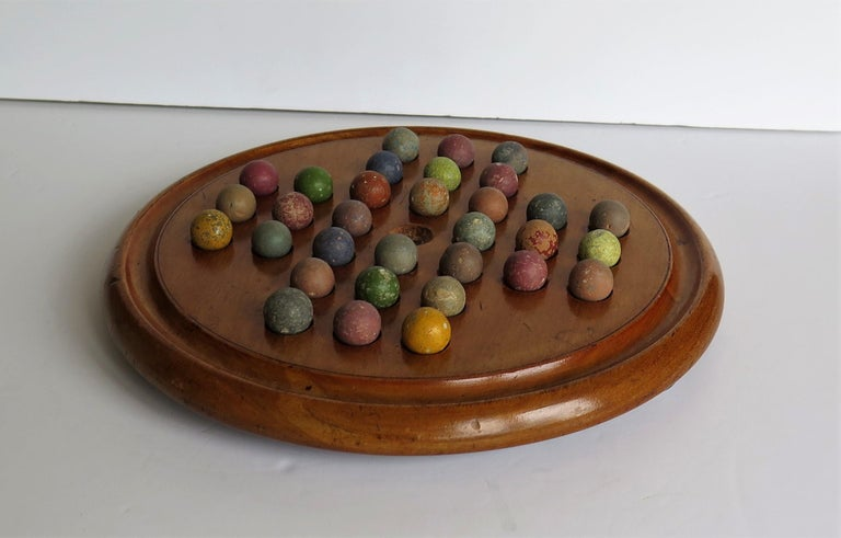 This is a complete Marble Solitaire Game, having a very good Mahogany board and a complete set of 32 clay or stone handmade marbles, all dating to the 19th Century Victorian period, or slightly earlier. 