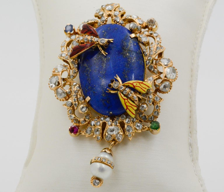 Exclusively from the Eiseman Estate Jewelry Collection, this early Victorian era Middle Eastern 14k yellow gold pin features a center oval lapis, 32.42x21.6mm. Surrounding the lapis is 3.00ctw of rose cut diamonds, J-K SI, one ruby (.30ctw), one