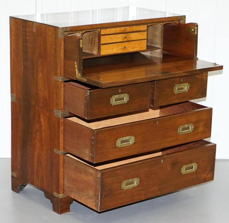 We are delighted to this lovely original late Victorian Military Campaign chest of drawers with drop front top drawer revealing a sliding secrataire desk  A good looking and compact desk in period lightly restored condition throughout, this piece