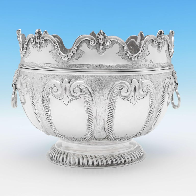 Hallmarked in London in 1890 by Aldwinckle & Slater, this striking, Victorian, antique sterling silver bowl, is in the 'Monteith' style, with a removable scalloped rim, lion mask drop ring handles, a fluted foot and chased decoration throughout. The