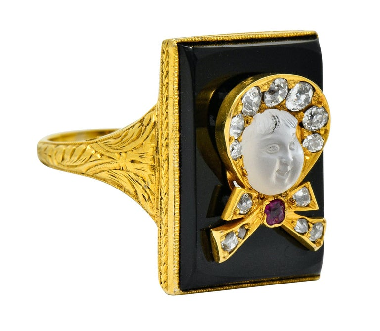 Rectangular statement ring designed as an ornately engraved mounting featuring a bezel set tablet of onyx with excellent polish  Centering a dimensional depiction of a baby in a bowed bonnet accented by a cushion cut ruby  Face is a deeply carved