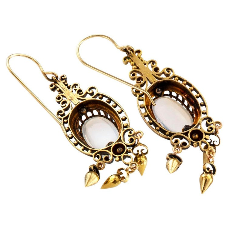 Victorian 1890s moonstone and gold pendent earrings. The articulated designs feature a pair of oval moonstones set in open work frames decorated with rounds beads and scrolling motifs, terminating with a fringe of teardrop-shaped beads and endowed