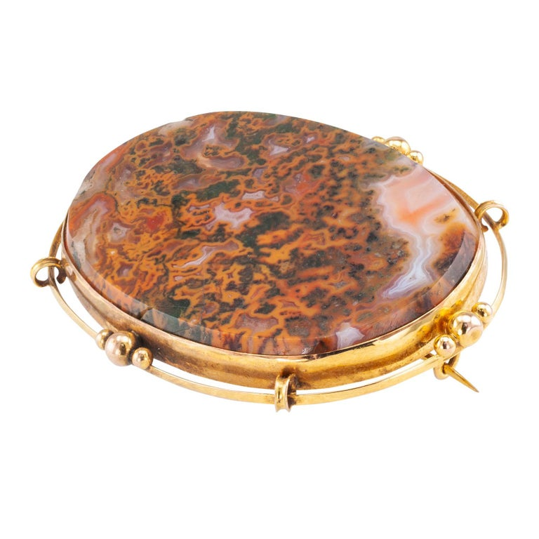 """Victorian moss agate and yellow gold brooch circa 1900.  DETAILS: GEMSTONES: one large oval flat-top moss agate stone.  METAL: 9-karat yellow gold.  MEASUREMENTS: approximately 2-5/16"""" (5.9 cm) horizontal width and 1-3/4"""" (4.4 cm) vertical"""