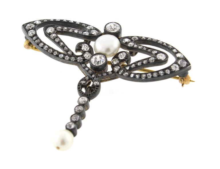 This Victorian diamond and natural pearl brooch features a detachable pearl drop. The  hand workmanship an impeccable example of Victorian design. ♦ Metal: Silver over gold ♦ 30 round diamonds=1.10 ♦ 60  mixed cut diamonds=.75 carat ♦ Circa: mid to