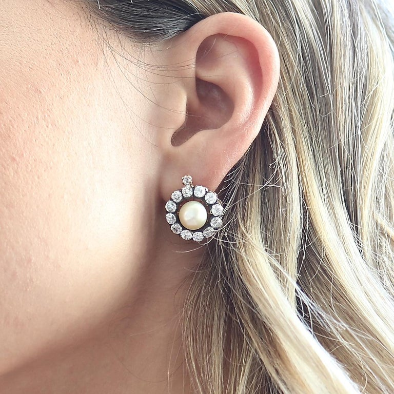 The everlasting bloom of nature captured with these natural pearl earrings. Featuring GIA certified natural salt water pearls that are surrounded by halos of old cut diamonds. Hand crafted in 18k gold resting on floating backs. Accompanied with the