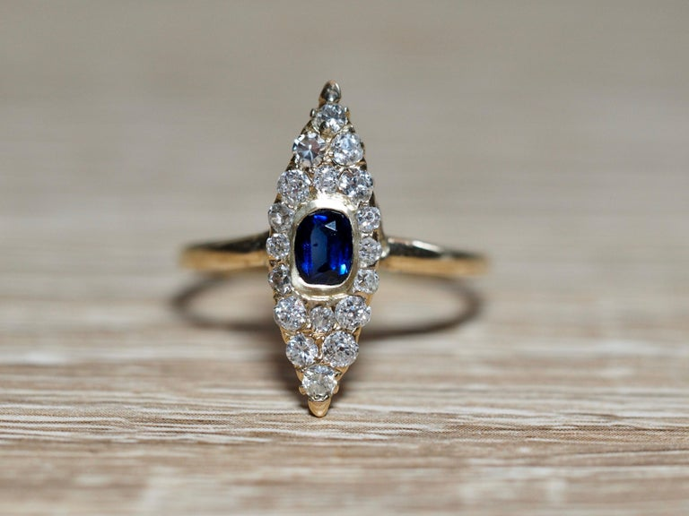 This Victorian Navette ring dates back to the early 1900's. The center is a deep royal 0.35 carat blue sapphire center illuminating in color. It is bezel set in a yellow gold frame sitting flush on the ring. The center is surrounded in the famous