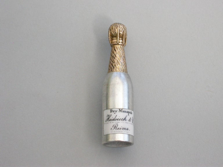 A rare Victorian Novelty silver Propelling Pencil modeled as a champagne bottle, with gilded top to imitate the foil and applied black and white enameled label for 'Heidssieck & Co, Reims'.